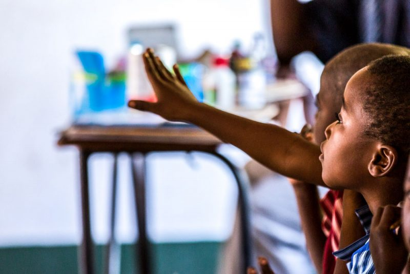child raises hand in African classroom in Zimbabwe